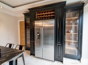 Fully Fitted Display Unit In Pitch Black Featuring Tall Pull Out Storage Units, Glass Display Doors & Led Back Lighting Finished With Wine Storage & Side By Side Refrigeration. Kitchens Crosby